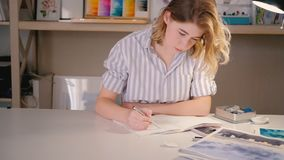 Young woman artist sketching drawing creating art. Backward tracking shot of young woman artist. Tidy home art studio workplace. Female sketching drawing stock footage