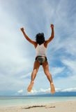 Backwards beach jump. Asian boy performing a backwards jump on a pristine tropical beach, arms stretched high and ascending to the sky stock images