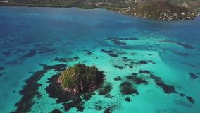 Backwards drone aerial view of a cay and island at the Caribbean. Surrounded by clear blue waters stock footage