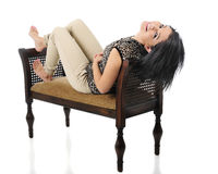 Backwards and Upside-Down. A beautiful teen girl reclined on a padded bench, looking back at the viewer with her head drapped over the edge. On a white stock photo