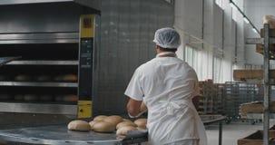 Backwarenindustriearbeitskräfte entluden das gekochte Brot von der Last der Ofenmaschine dann das Brot in den speziellen Regalen stock video