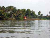 Backwaters of Kerala with a small hut. Fancy a ride through the jungle on a boat?  You've come to the right place.  The state of Kerala in South India has a Stock Photo