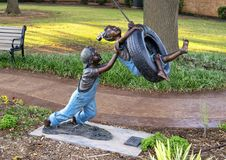 Backyard Adventure by Missy Vandable, bronze sculpture in Edmond, Oklahoma. Pictured is a bronze sculpture titled `Backyard Adventure` by Missy Vandable.  It is Stock Photos