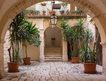 Backyard with arch, plants in pots, stairs and lantern. Patio decoration. Ancient courtyard background. Medieval architecture. Beautiful backyard with arch stock images