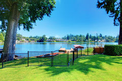 Backyard area with well kept lawn and metal fence. Beautiful water view Stock Image