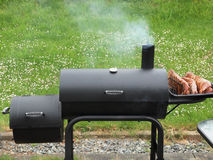 Backyard barbequing on a charcoal smoker Stock Images