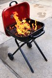 Backyard bbq. Flaming charcoal barbecue in backyard Stock Images