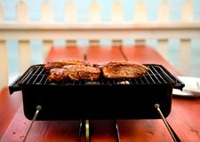Backyard BBQ. On picnic table with white picket fence for background Stock Image
