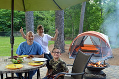 Backyard camping. A family, enjoying backyard camping, poses for a photo while waiting for their home cooked barbecued meal Royalty Free Stock Images