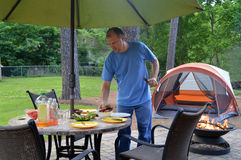 Backyard camping. Man arranging food on a table next to a burning fire and a tent in a backyard campsite Stock Photo