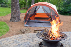 Backyard camping. A tent and a campfire on a backyard Royalty Free Stock Image