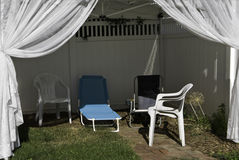 Backyard Canopy. A backyard canopy with lounge chairs and drapes on green grass and brick path Stock Photography