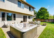 Backyard Concrete Floor Patio Area With Hot Tub. Well Kept Lawn Around.  Stock Images