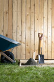 Backyard concreting, garden DIY project and tools. A backyard, DIY, home garden concreting project with wheelbarrow, shovel, wooden fence, wet cement and form Stock Photo