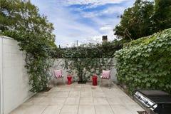 Backyard cozy patio area with wicker furniture set. Backyard cozy patio area with wicker  furniture set Stock Photo