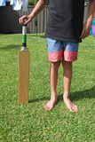 Backyard Cricket. A boy standing holding a cricket bat in a surburban backyard. Backyard cricket is classic Australian backyard summer activity Royalty Free Stock Images