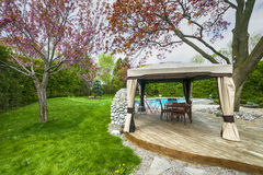 Backyard deck and gazebo. Backyard of residential house in spring with wooden deck and gazebo Stock Photography