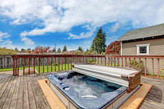 Backyard deck with jacuzzi. Backyard wooden deck with jacuzzi on it. Close up view of open jacuzzi and water in it Royalty Free Stock Photography