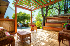 Backyard deck with wicker furniture and pergola. Royalty Free Stock Image