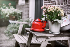 Backyard decoration with vintage kettle and flowers. On small wooden table stock image
