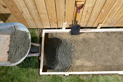 DIY home concreting project with wet cement. A backyard, DIY home concreting project with wet cement, wheelbarrow, shovel, wooden fence and form work Royalty Free Stock Images