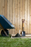 DIY, home concreting project with wheelbarrow. A backyard, DIY, home concreting project with wheelbarrow, shovel, wooden fence, fresh cement and form work Royalty Free Stock Photography