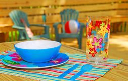 Backyard Entertaining. Colorful place setting on shaded back porch ready for entertaining Royalty Free Stock Image