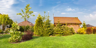 Backyard of a family house. Landscaped garden with green mown grass, wood shelter. Stock Image