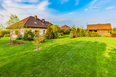 Backyard of a family house. Spacious landscaped garden with green mown grass Royalty Free Stock Photography
