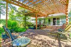 Backyard farm deck with attached open pergola. Great idea for farm house backyard. Big wood deck extended to pergola with small garden pond Stock Images