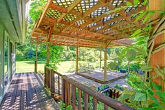 Backyard farm deck with attached open pergola. Farm house backyard deck view. Pond and waterfall, covered patio area with rustic old bench and flower pots Stock Photography