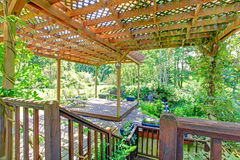Backyard farm deck with attached open pergola. Farm house backyard deck view. Pond and waterfall, covered patio area with rustic old bench and flower pots Stock Images