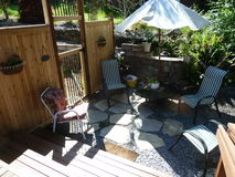 Backyard fence and garden area. Side yard off of deck with lawn chairs, umbrella and small table with gravel and flag stone pavers adjacent to fenced in garden Stock Photo