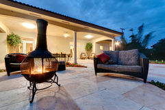 Backyard Fire Pit. Fire pit in a modern backyard with patio furniture Royalty Free Stock Photos