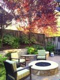 Backyard with firepit in fall. Backyard with fire pit in fall with patio furniture colorful trees stock image
