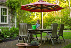 Backyard Fun. Young Girl Playing With A Bucket On A Teak Patio Table With Umbrella Royalty Free Stock Photos