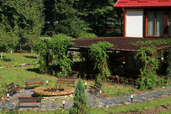 Backyard garden. Big garden with benches, fountain and lots of green Royalty Free Stock Photography