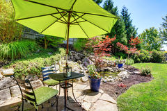 Backyard garden with beautiful landscape. Patio area with umbrella, table and chairs. Northwest, USA Stock Image