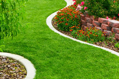 Backyard garden. Backyard with colorful flowers and green lawn Stock Photos