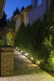 Backyard Garden Path at Night. Backyard Garden Pavers Path Brick Column with Bronze Crane at Night Stock Photo