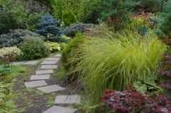 Backyard Garden Path. A tiled garden path wends its way through a wooded backyard garden Royalty Free Stock Images