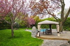 Backyard with gazebo and deck. Residential  backyard with gazebo, deck, stone patio and swimming pool Stock Photo