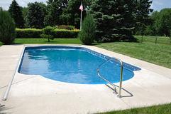 Backyard In-Ground Swimming Pool. On a Sunny Summer Day Royalty Free Stock Image