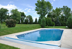 Backyard In-Ground Swimming Pool. On a Sunny Summer Day Royalty Free Stock Images