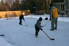Backyard Hockey. Father playing a game of hockey in the backyard with his kids Stock Photo
