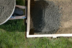 Backyard home concreting project with wet cement. A backyard, DIY home concreting project close up with wet cement, wheelbarrow and form work Stock Photo