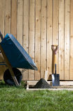 Backyard, home concreting project with wheelbarrow. A backyard, home concreting project with wheelbarrow, shovel, wooden fence, fresh cement and form work Stock Image