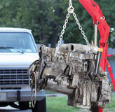 Backyard Home Mechanic. An engine hanging from a hoist during home engine repair or replacement.  Focus on engine.  Names and part numbers have been removed or Stock Photos