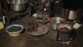 Close-up view of young african woman preparing dinner alone on burning coals for her family on a backyard of the house. On a backyard of the house. Housewife stock video