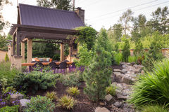 Backyard Landscape Design. An custom designed shelter is seen beyond a perennial garden featuring a dry stream bed Royalty Free Stock Photos